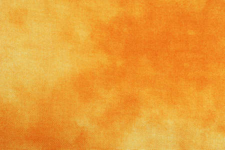 Macro of orange tie-dyed fabric for background use.