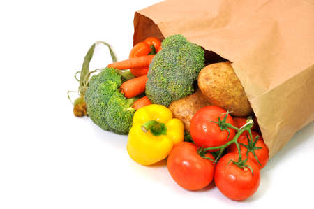 Vegetables in grocery bag isolated on white background.