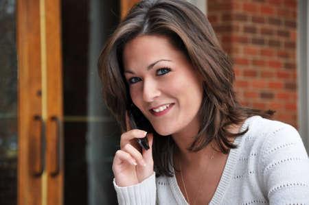 maglioni: Closeup di giovane donna parlando sul cellulare e guarda a porte chiuse.