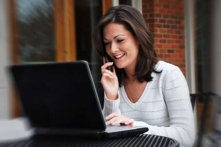 Young woman talking on cell phone and using laptop.