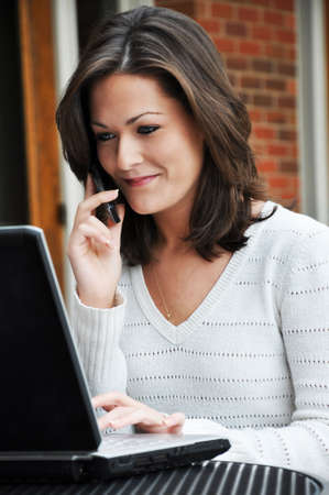 Young woman talking on cell phone and using laptop. photo