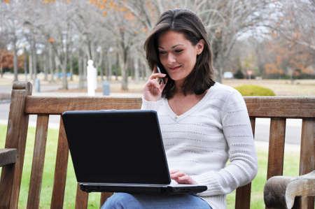 携帯電話で話しているとラップトップを使用して公園のベンチに座っていた若い女性。 写真素材