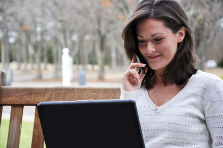 Young woman sitting on bench in park talking on cell phone and using laptop. photo