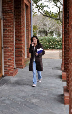 woman on phone: Female student walking to class holding books and talking on cell phone. Stock Photo