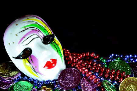 masquerade masks: Mardi Gras mask with beads and doubloons on black background with copy space.  Stock Photo