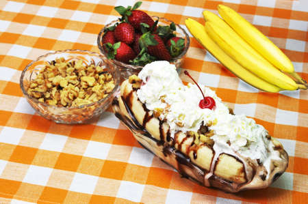 Banana split with walnuts, strawberries and bananas in background. photo