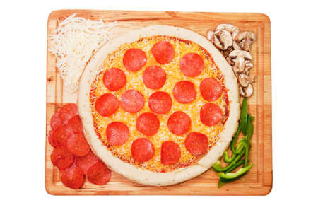 Uncooked pepperoni pizza on wooden cutting board with ingredients. Isolated on white background with path. photo