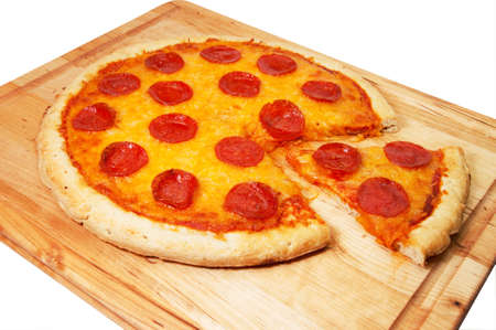 Whole pepperoni pizza with slice removed on cutting board.  Isolated on white background. photo