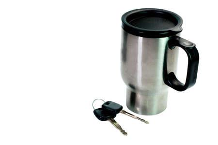 白い背景に分離されたコーヒーのマグカップと車のキー