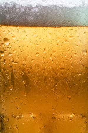 Macro of beer in cold glass showing condensation.