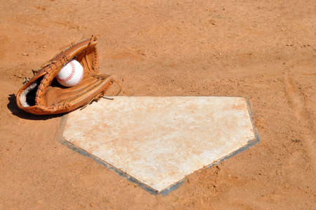 Baseball and glove on the corner of home plate.