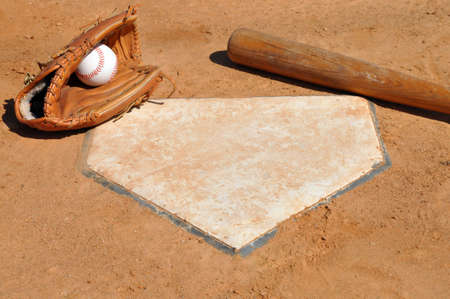 Baseball, glove, and bat on home plate.