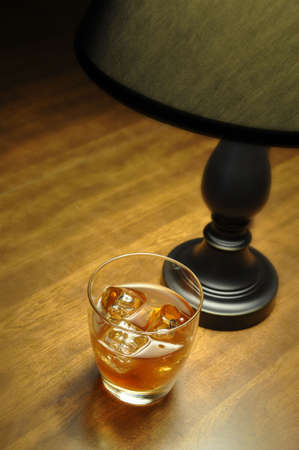 Bourbon on the rocks on wooden table illuminated by lamp. Stock Photo - 4417072