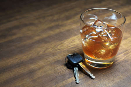 Glass of whiskey and car keys on wooden table. Standard-Bild