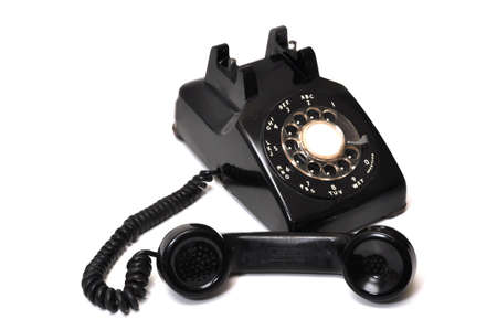 Vintage black rotary telephone off the hook.  Isolated on white background.