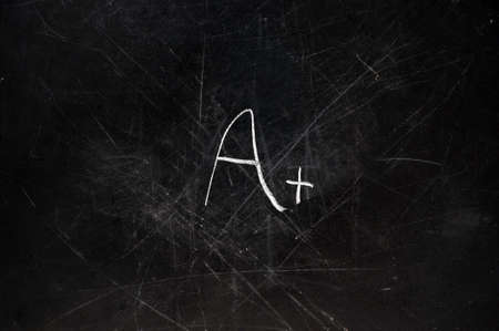 A+ grade on black chalkboard with copy space.  Chalk dust on board.  photo