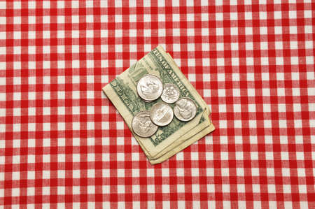 Tip left on restaurant table.  Bills and coins on red gingham tablecloth.   photo