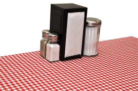 Table with red gingham tablecloth at diner.  Isolated on white background
