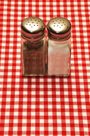 Salt and pepper shakers on red gingham tablecloth. Zdjęcie Seryjne