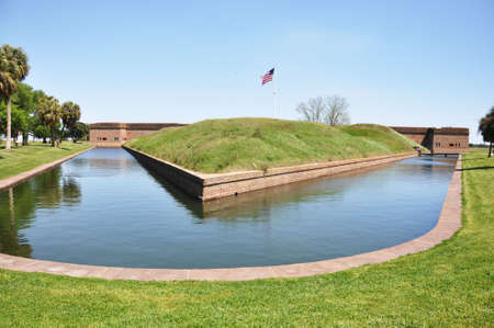 Moat surrounding Fort Pulaski, Georgia with American flag.   photo