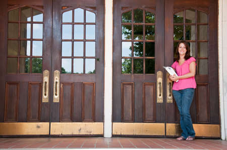 Female college student holding books and standing at front door of school.   photo