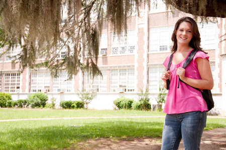 Female college student standing in front of school with backpack.   photo