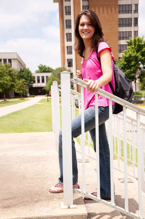 Female college student standing on steps in front of school with backpack.