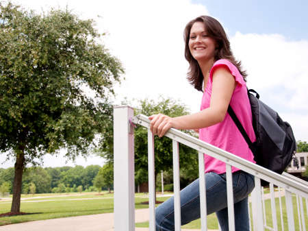 Female college student standing on steps in front of school with backpack.  Stock Photo