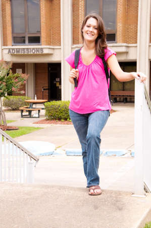 admissions: Female college student with backpack leaving admissions office at university.   Stock Photo