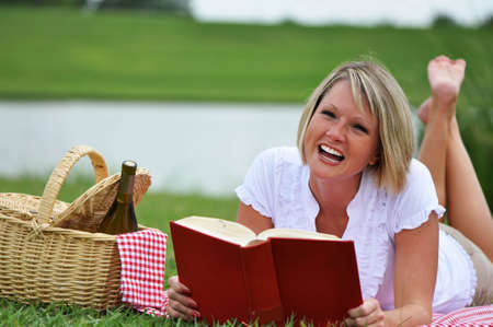 Young blond woman on picnic with book and wine.  Picnic basket with gingham blanket and napkin. photo