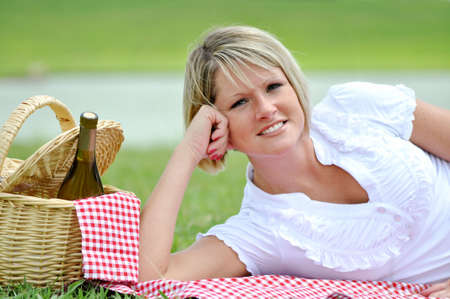 Young blond woman on picnic beside lake with wine and basket.  Lying on gingham blanket. photo