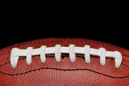 黒の背景に分離されたアメリカン ・ フットボールのクローズ アップ。 写真素材