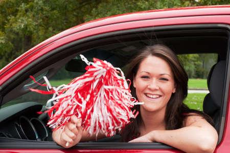 Female student sitting in car with pom pom. photo