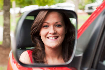 Female portrait of attractive brunette in vehicle mirror.