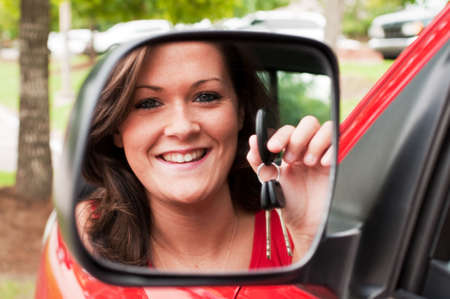 Attractive young brunette holding vehicle keys in rear view mirror.