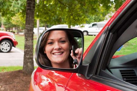 rear view mirror: Las llaves del veh�culo atractivo joven morena de explotaci�n en el espejo retrovisor.