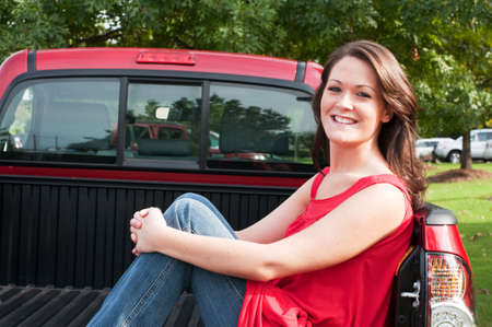 truck driver: Attractive female brunette sitting in bed of red pickup truck.