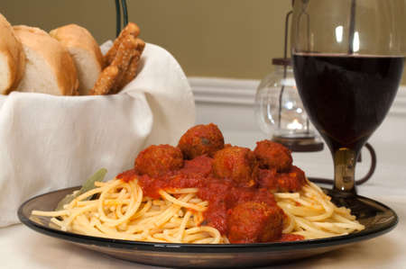 Spaghetti and meatballs dinner with red wine, garlic bread, and breadsticks.