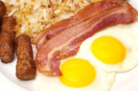 Breakfast plate with eggs sunny side up, bacon, link sausage, and hash browns.