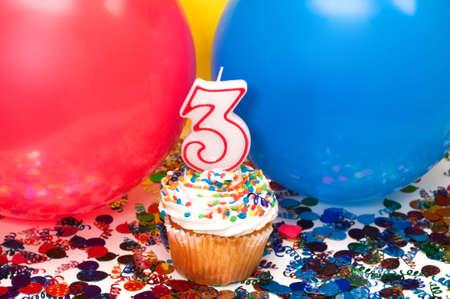 風船、紙吹雪、カップケーキ、数 3 キャンドルでお祝い。 写真素材