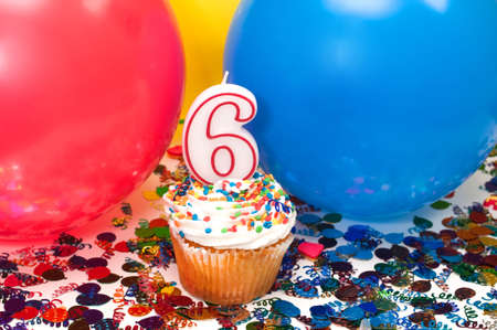 Celebration with balloons, confetti, cupcake, and number 6 candle. photo