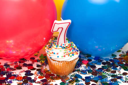 seventh: Celebration with balloons, confetti, cupcake, and number 7 candle. Stock Photo