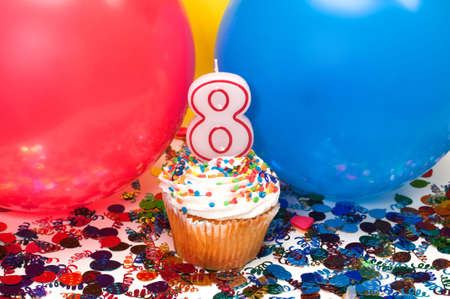 Celebration with balloons, confetti, cupcake, and number 8 candle. photo