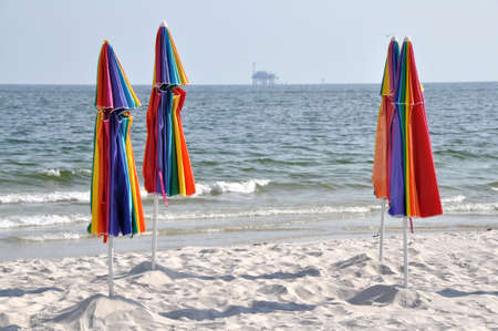 Abandoned beach with closed umbrellas.  Off shore oil rig in background. photo