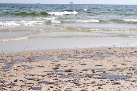 Oil spill on beach with off shore oil rig in background. Stock Photo