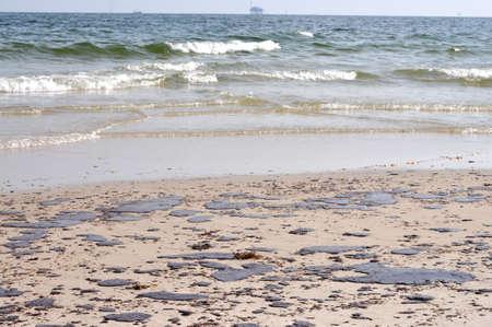 oil spill: Sversamento di petrolio sulla spiaggia con off shore olio rig in background.  Archivio Fotografico