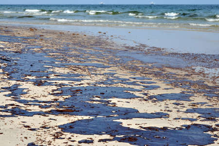 Oil spill on beach with oil skimmers in background. Stock Photo