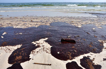 spills: Oil spill on beach with off shore oil rig in background. Stock Photo
