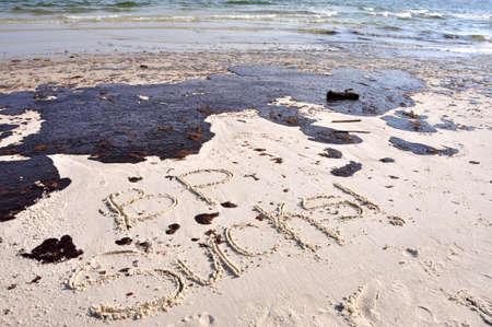 glob: BP oil spill on Gulf of Mexico beach.  BP SUCKS Written in sand.