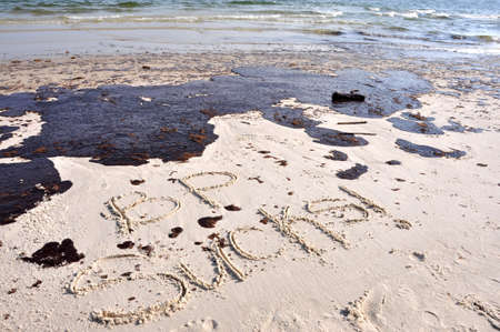 körfez: BP oil spill on Gulf of Mexico beach.  BP SUCKS Written in sand.